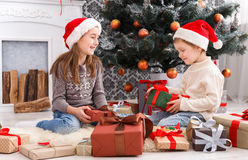 Happy children in santa hats unwrapping christmas presents Stock Image