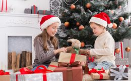 Happy children in santa hats unwrapping christmas presents Stock Images