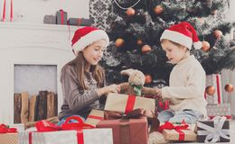 Happy children in santa hats unwrapping christmas presents Royalty Free Stock Photos
