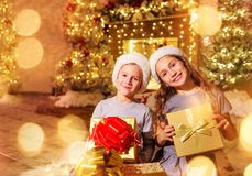 Happy children in Santa`s hats with gifts in the room Christmas. royalty free stock image