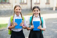 Happy children in school uniforms hold study books outdoors, knowledge