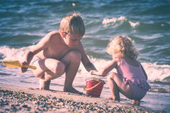 Happy children on a sea. Instagram stylisation. Little brother and sister playing with sand on a sea beach. Happy children. Instagram stylisation stock photo