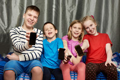 Happy children show mobile phones Stock Image