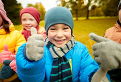 Happy children showing thumbs up in autumn park Royalty Free Stock Images