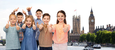 Happy children showing thumbs up over london Royalty Free Stock Image