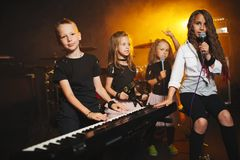 Children singing and playing music in recording studio. Happy children singing and playing music in recording studio royalty free stock photos