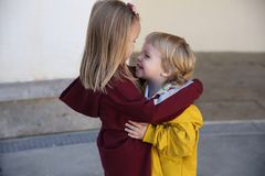 Happy children boy and girl dressed in hoodie cuddle, showing love for each other royalty free stock photos