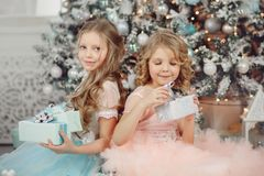 Happy children sister open magic gift home near tree in dress. Merry Christmas. stock image
