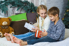 Happy children sitting on bed and holding gifts Royalty Free Stock Photos