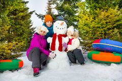 Happy children sitting close to cheerful snowman Stock Photo