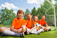 Happy children sitting together on field grass Royalty Free Stock Images