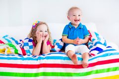 Happy children sleeping under colorful blanket. Two kids sleeping in bed under colorful blanket. Children relaxing in bedroom. Tired toddler girl and baby boy Royalty Free Stock Image