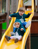 Happy children on slide at playground. Two happy children in jackets on slide at playground in autumn Royalty Free Stock Image