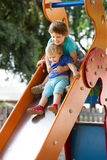 Happy children on slide Royalty Free Stock Images