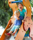 Happy children on slide stock photography
