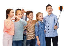 Happy children with smartphone and selfie stick Stock Image