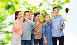 Happy children with smartphone and selfie stick Stock Images