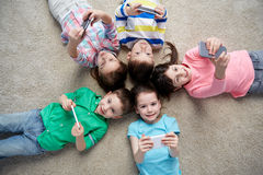 Happy children with smartphones lying on floor Royalty Free Stock Photography