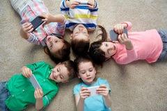 Happy children with smartphones lying on floor Stock Photos