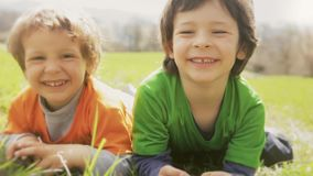 Happy children smiling close up portrait. Two brother kids laughing and playing while lay down on grass meadow in