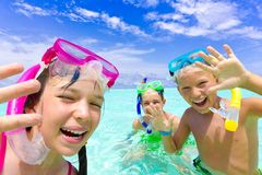 Happy children snorkeling. Three happy children snorkeling in tropical sea with blue sky and cloudscape background Royalty Free Stock Photography