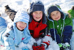 Happy children in snow. A view of three happy children playing together in the winter snow Royalty Free Stock Photos