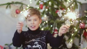 Happy boy burn sparklers among bokeh lights and garlands on a Christmas tree. slow motion. 3840x2160 stock footage