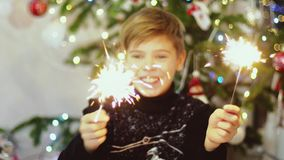Happy boys burn sparklers among bokeh lights and garlands on a Christmas tree stock video footage