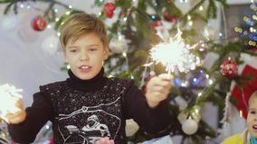 Happy boys burn sparklers among bokeh lights and garlands on a Christmas tree. slow motion. 3840x2160 stock footage