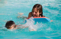 Happy Children Splashing In Pool. Brother and sister swimming and laughing in a clear, blue pool Royalty Free Stock Images