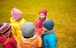Happy children standing in circle at autumn park Royalty Free Stock Images