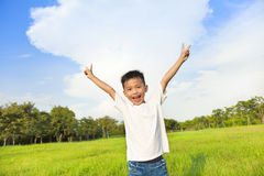 Happy children standing on meadow and raise hands Royalty Free Stock Photography