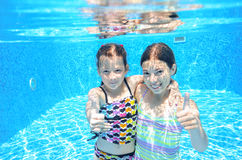 Happy children swim in pool underwater, girls swimming. Playing and having fun, kids water sport royalty free stock photography