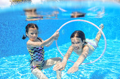 Happy children swim in pool underwater, girls swimming. Playing and having fun, kids water sport stock photography