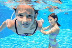 Happy children swim in pool underwater, girls swimming Stock Photos