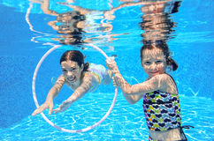 Happy children swim in pool underwater, girls swimming. Playing and having fun, kids water sport Royalty Free Stock Images