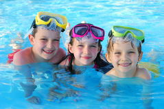 Happy children swimming. Happy portrait of children swimming with goggles on head