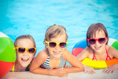 Happy children in the swimming pool. Funny kids playing outdoors. Summer vacation concept stock photography