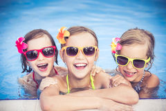 Happy children in the swimming pool. Funny kids playing outdoors. Summer vacation concept Stock Photos
