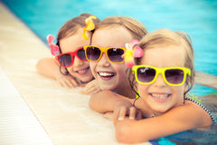 Happy children in the swimming pool. Funny kids playing outdoors. Summer vacation concept Stock Images