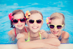 Happy children in the swimming pool. Funny kids playing outdoors. Summer vacation concept royalty free stock images