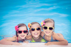 Happy children in the swimming pool. Funny kids playing outdoors. Summer vacation concept stock photo