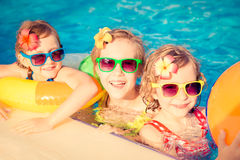 Happy children in the swimming pool. Funny kids playing outdoors. Summer vacation concept stock image