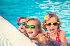 Happy children in the swimming pool. Funny kids playing outdoors. Summer vacation concept royalty free stock photos