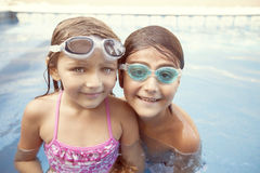 Happy children in swimming pool. Happy children having fun in swimming pool with goggles royalty free stock photos