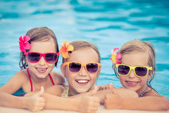 Happy children in the swimming pool. Happy children showing thumbs up in the swimming pool. Funny kids playing outdoors. Summer vacation concept royalty free stock image