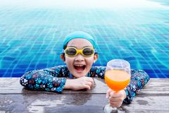Happy Children at the Swimming Pool Side, Girl Relaxing with Sum. Mer Drink, Smile and Looking at Camera, Blue Water as background Royalty Free Stock Images