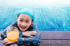 Happy Children at the Swimming Pool Side, Girl Relaxing with Sum. Mer Drink, Smile and Looking at Camera, Blue Water as background stock images