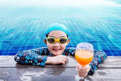 Happy Children at the Swimming Pool Side, Girl Relaxing with Sum. Mer Drink, Smile and Looking at Camera, Blue Water as background Stock Image