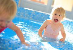 Happy children in swimming pool. Two happy children girl in swimming pool stock photo